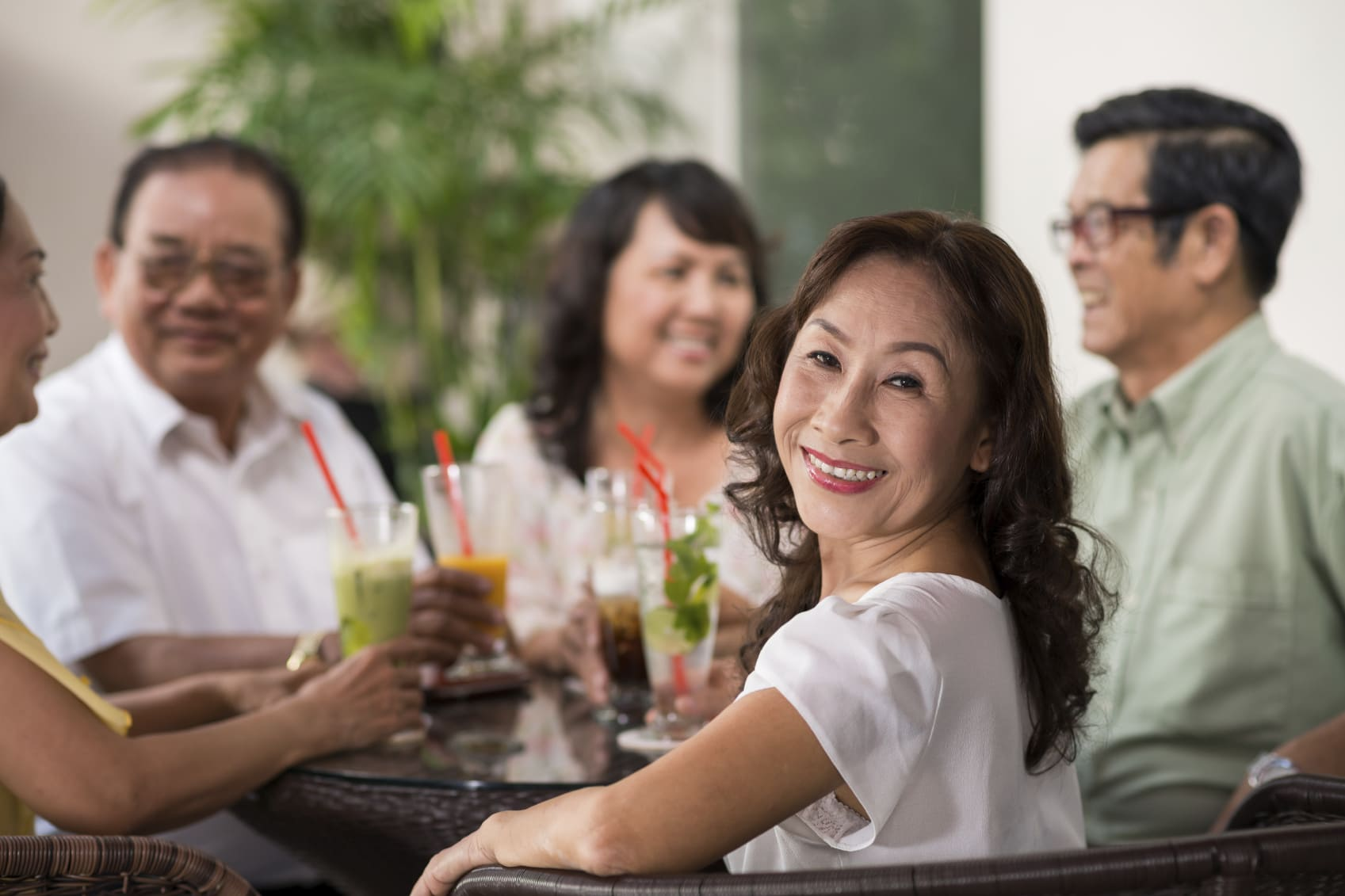 Pretty aged woman at party with her friends looking backward