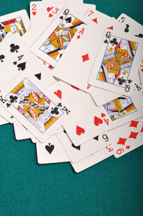 heap of playing cards on a green cloth background