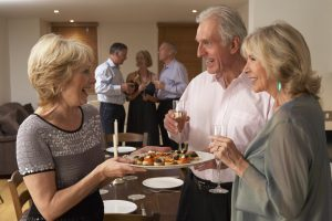 Woman Serving Hors D'oeuvres To Her Guests and Friends At A Dinner Party