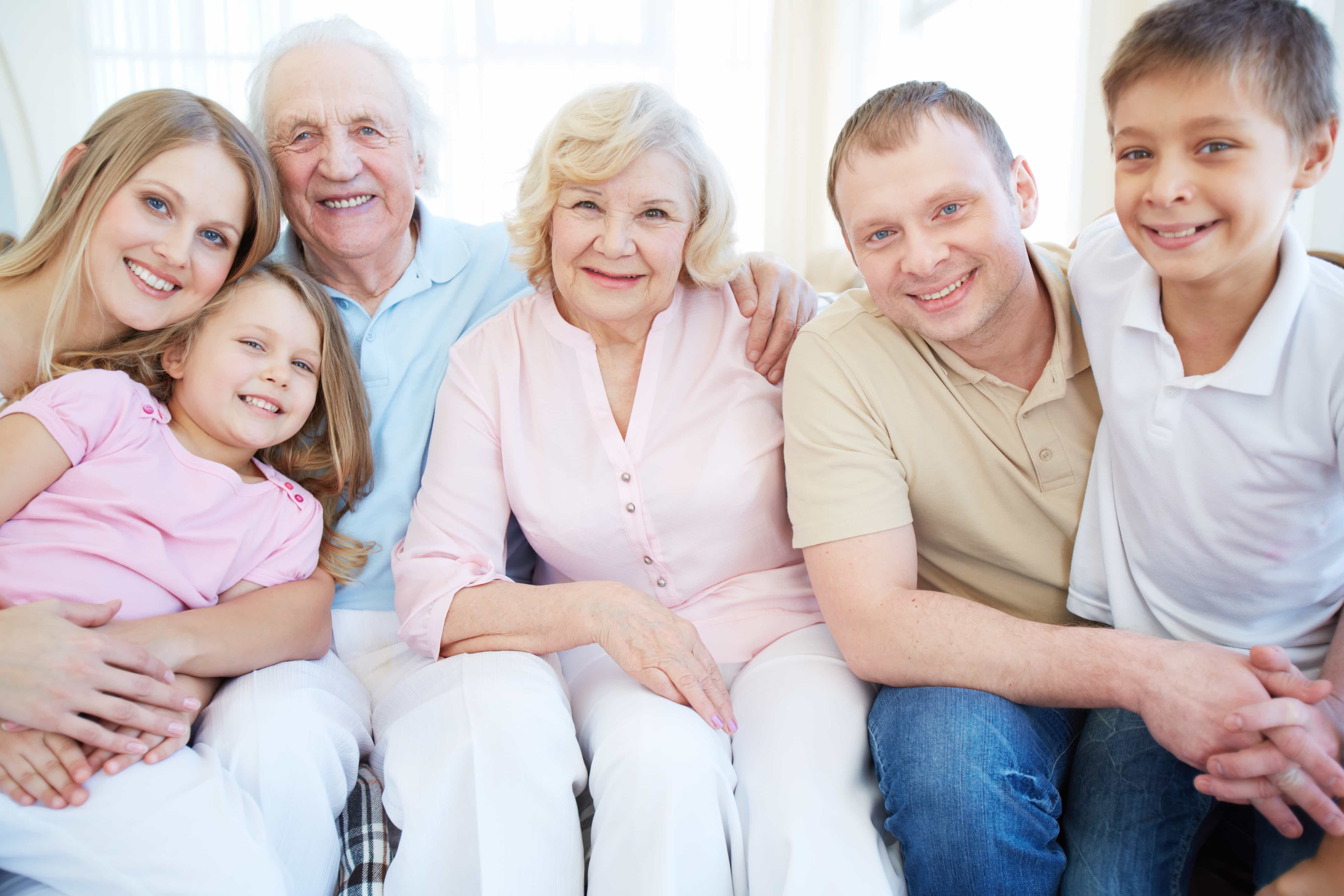 Portrait of senior and young couples with their children looking at camera at home
