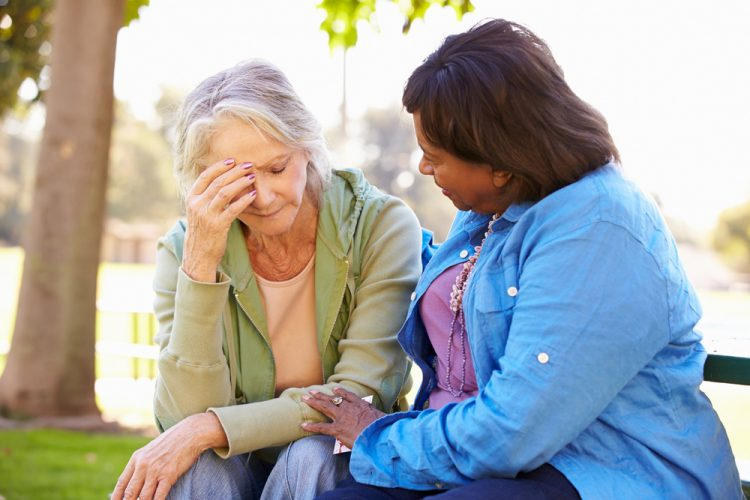 senior Woman Comforting Unhappy Senior Friend Outdoors
