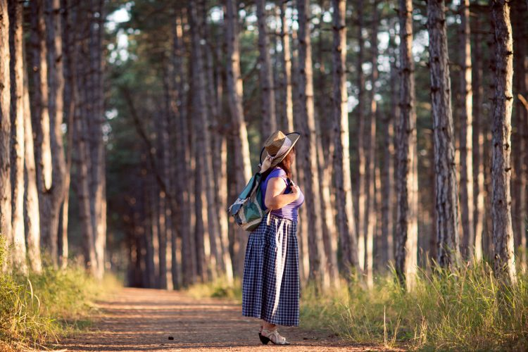 Happy senior woman in a straw hat with backpack walking through the forest. Nature outdoor activity. Healthy lifestyle concept. Chartwell Retirement Residences