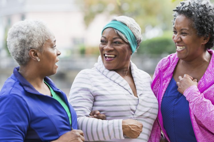 A group of three senior African American women standing together at the park, smiling, laughing and talking.